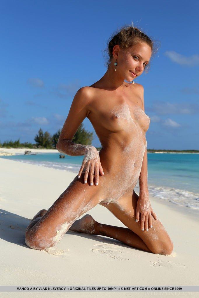 Стройная милашка позирует на фоне красивого пейзажа, стоя на белом песке около голубой воды