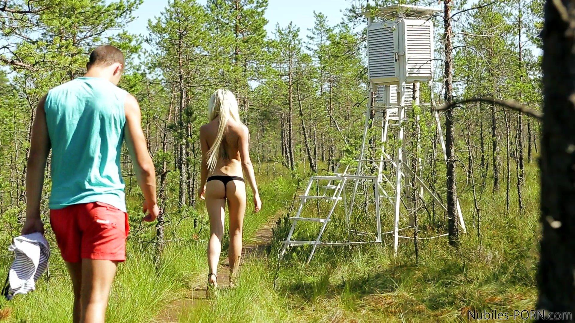 Блондинка гуляет по лесу с парнем, которого норовит соблазнить своей шикарной задницей, у нее все выходит