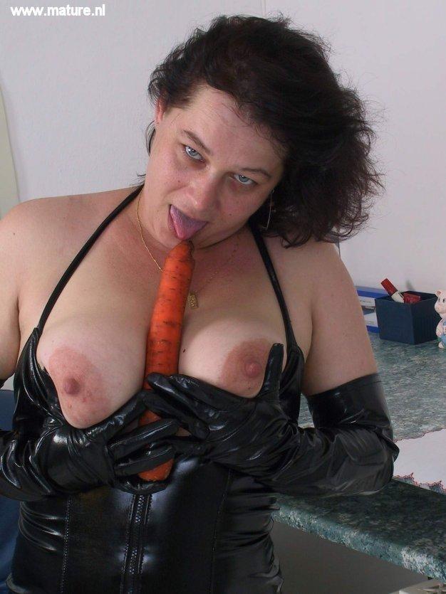 Пухлая баба фанатка БДСМ, она надела кожаный корсет и трахнула себя морковкой на кухне