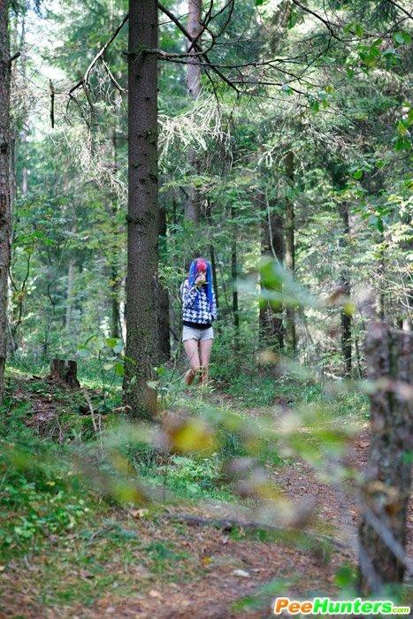 Девушка в лесу на природе присела пописать приспустив с себя штаны