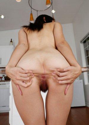 Темноволосая девушка устроилась на кухонном столе голая и раздвинула ягодицы