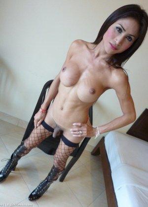 Темноволосый трансвестит в сексуальном черном белье позирует на камеру, показывая небольшие сиськи и член