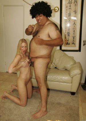 Развратная блондинка с небольшой грудью возбудилась и решила пососать хуй толстому мужику, сидящему на диване