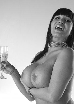 Игривая брюнетка облизывает свои здоровенные сиськи шампанским