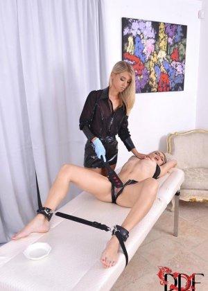 Госпожа блондинка, связав свою рабу по рукам и ногам, умело занимается с ней фистингом