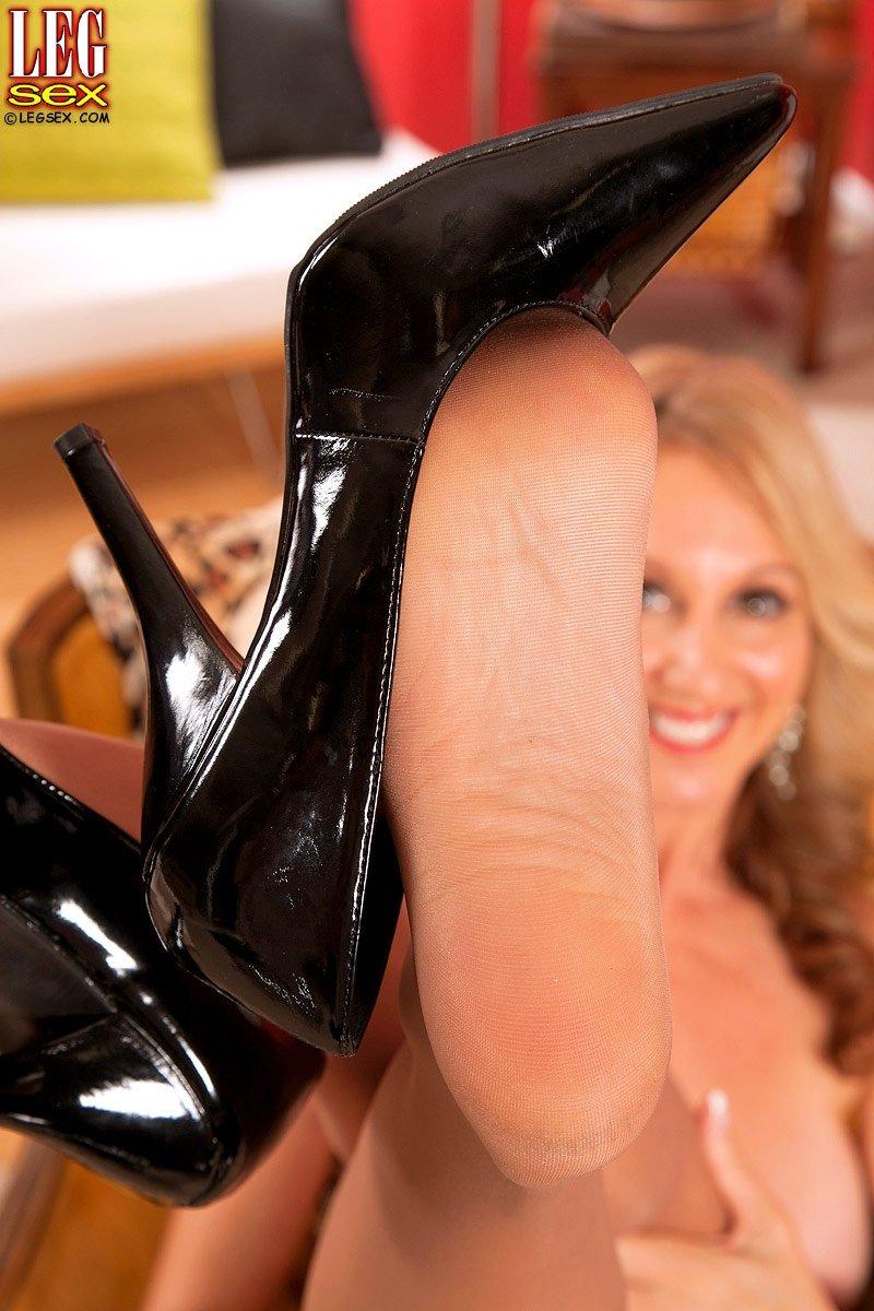 Улыбчивая зрелая женщина с большими сиськами показывает свои ножки