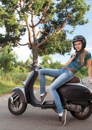 Девушка в шлеме, но без трусов стоит у мотороллера