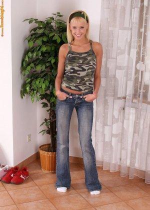 Веселая блондинка снимает джинсы