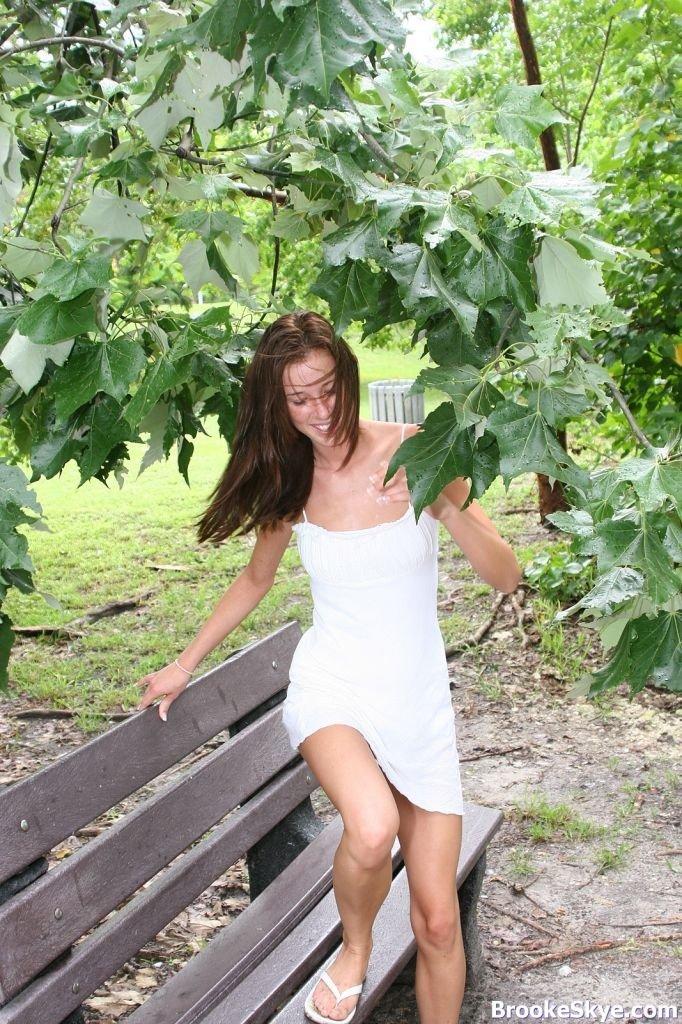 Девушка в белом платье без трусиков, показывает пизду лежа на лавочке в парке