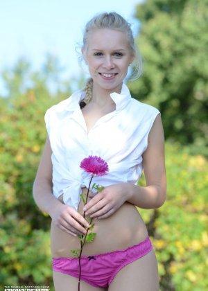Голая блондинка нюхает аленький цветочек