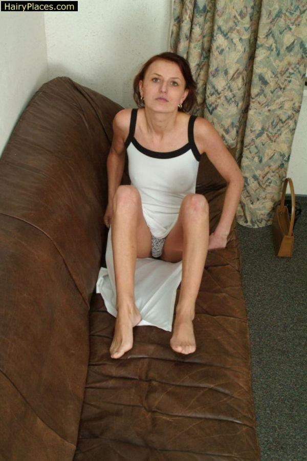 Лежит на диванчике и вгоняет пальчики в волосатое влагалище