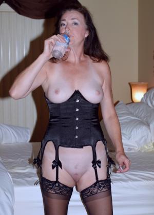 Зрелая женщина в чулках и в корсете