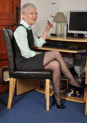 Зрелая блондинка в черных чулках попозировала обнаженной в офисе