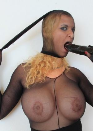 Блондинка в черных колготках на голове сует себе в промежность большой член