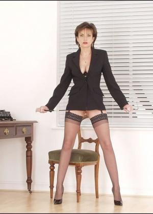 Сидит на стуле и демонстрирует промежность женщина в черных чулках