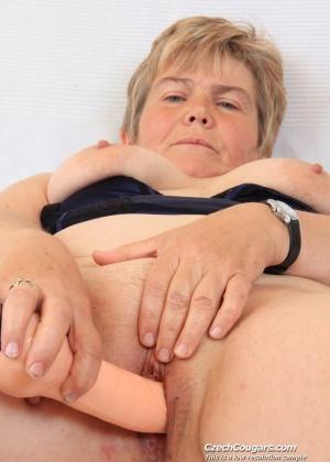 Зрелая тетка в черных чулках сует себе в пизду резиновый член без эмоций