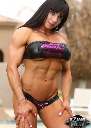 Мускулистая женщина с большими дойками позирует под открытым небом