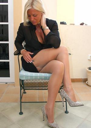 Зрелая блондинка эротично раздевается на стуле
