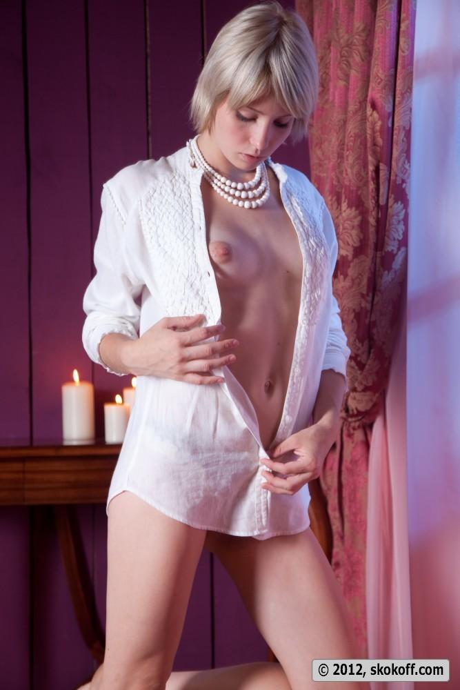 Очаровательная блондинка с короткими волосами позирует в разных позах обнаженной