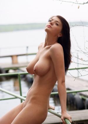 Грудастая красавица позирует голой в лесу