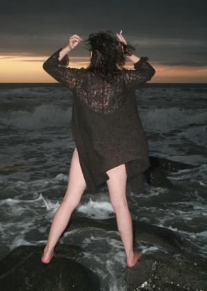 Женщина 42 лет ходит полуголая на скалистом берегу