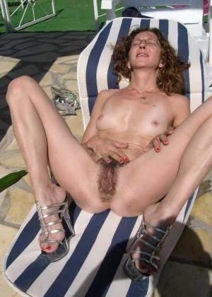 Женщина загорает на солнце и одновременно ебет себя длинным огурцом
