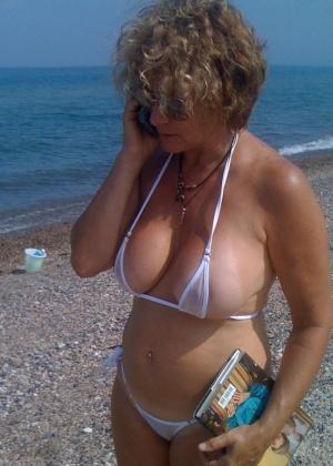 Пожилая дама в прозрачном бикини на пляже