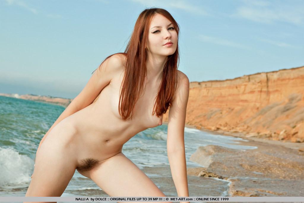Показывает пушистый лобок на пустом пляже