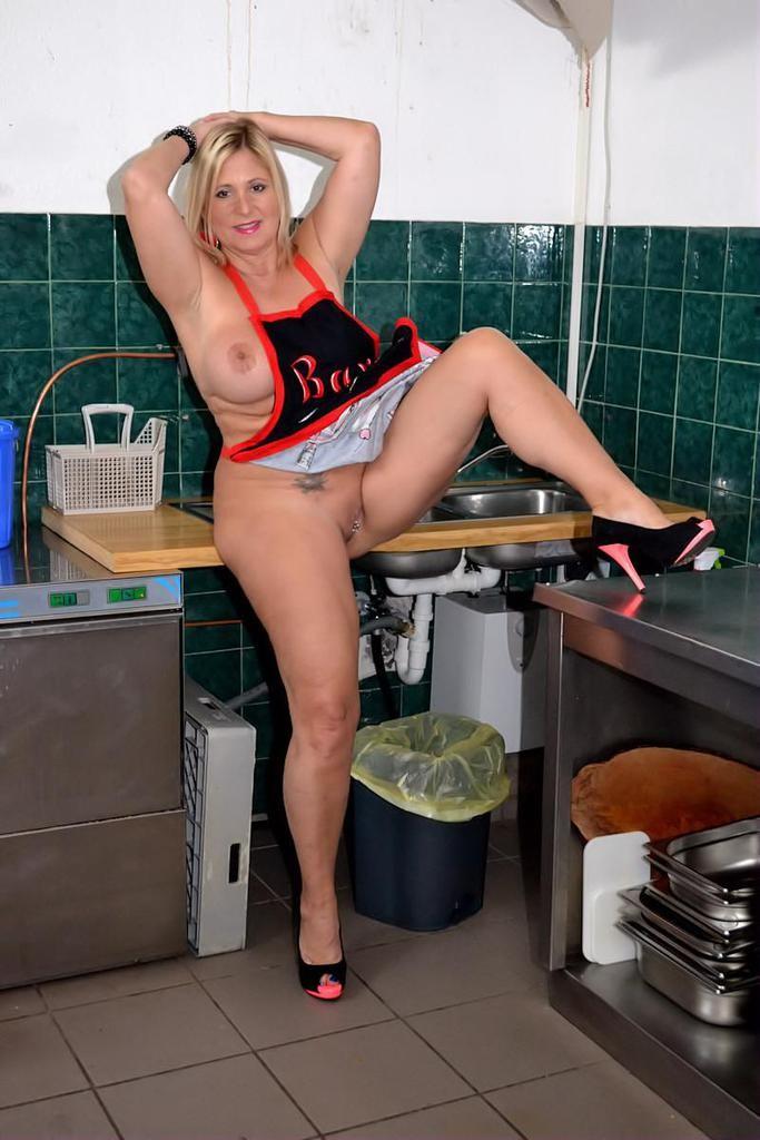 Пышная домохозяйка блондинка готовит голая на кухне