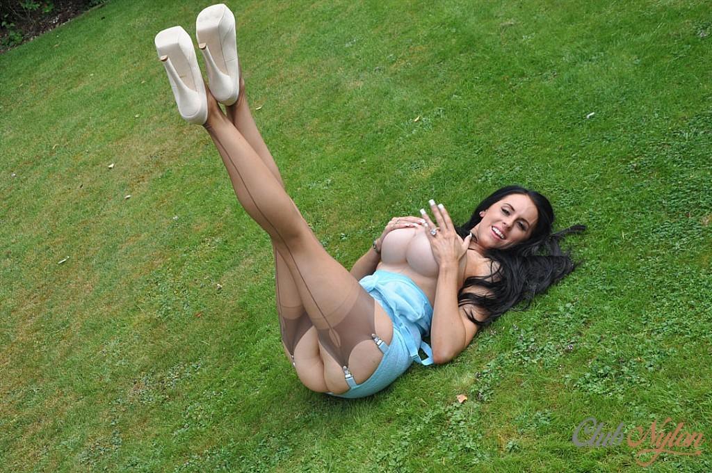 Сексапильная милфа в чулках под коротким платьем лежит на траве
