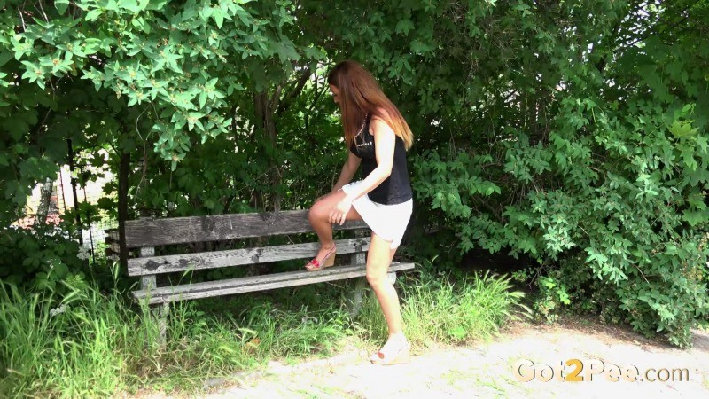 Солидная длинноногая девка писает в парке на скамейку