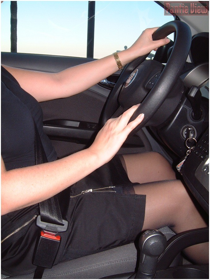 Playful wife driving car and flashing her pantyhose