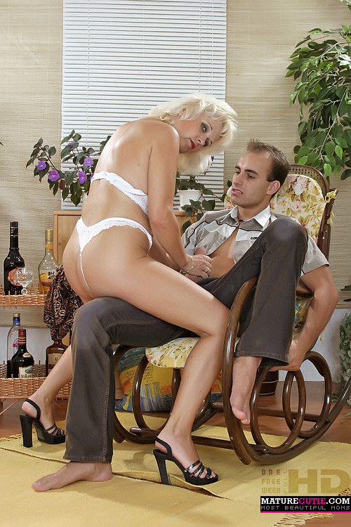 Пожилая блондинка трется пиздой об ногу и дрочит член парню
