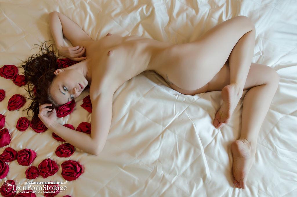 Голая девушка на кровати с лепестками роз