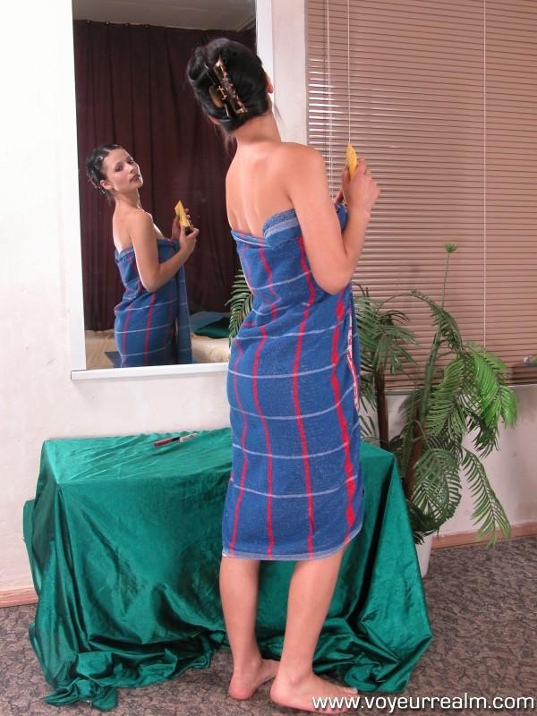 Брюнетка сама восхищается своей наготой рассматривая себя в зеркале