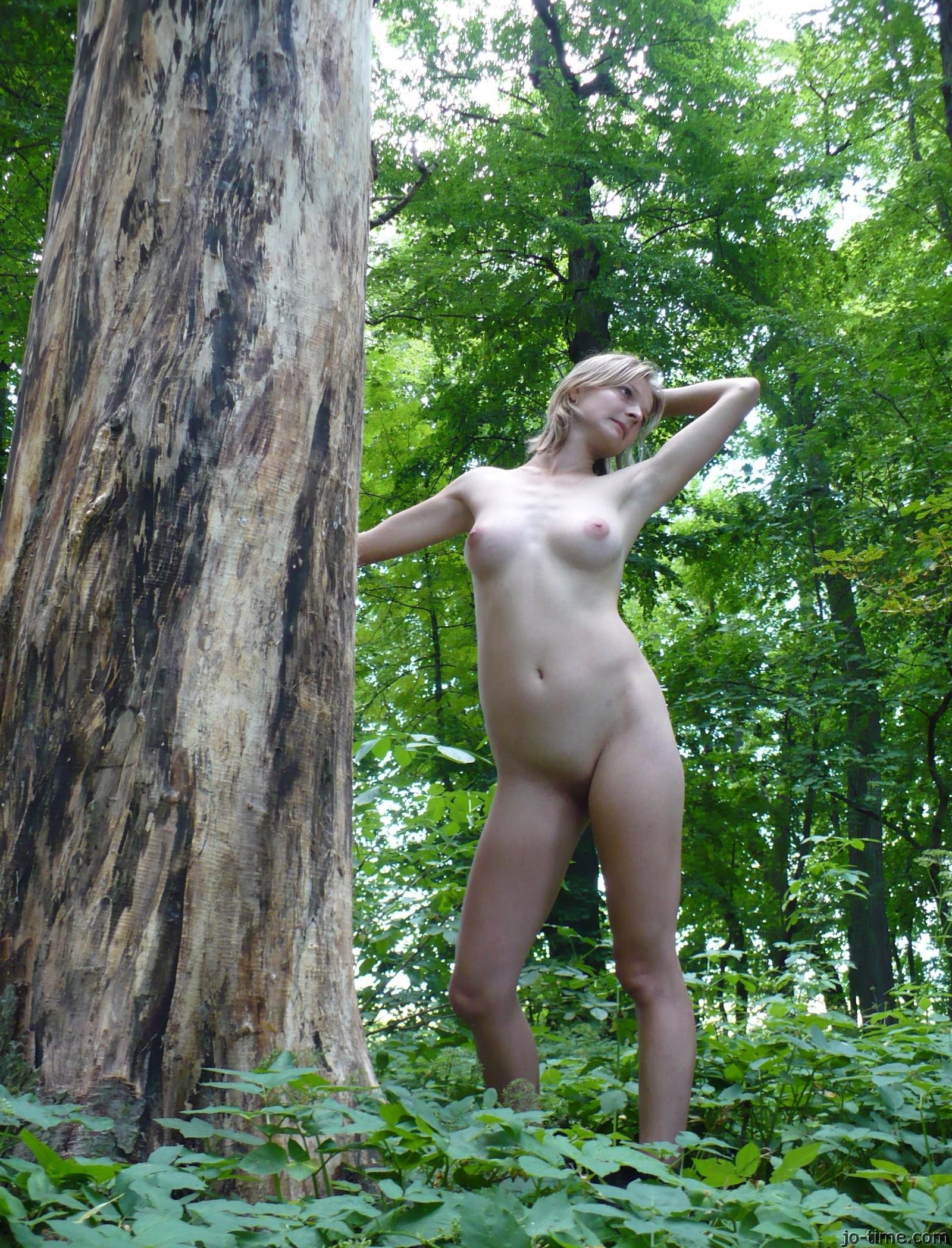 Молодая спорстменка позирует голая на природе