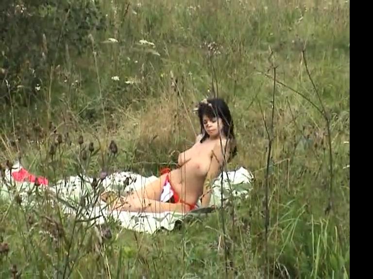 Молодая девушка с большими сиськами загорает на лужайке топлесс
