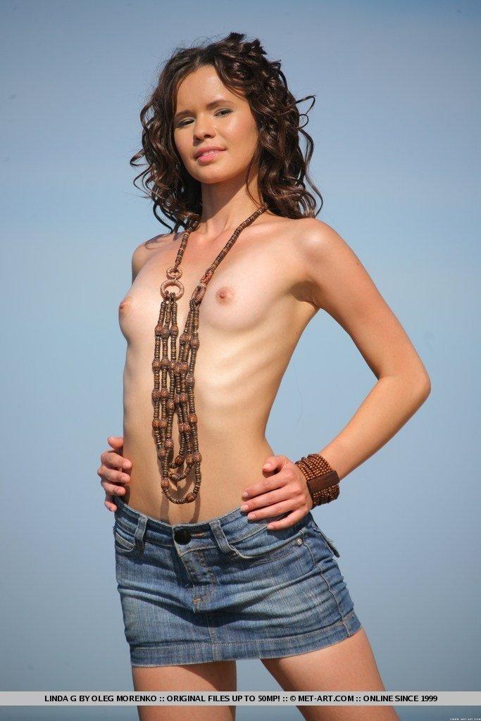 Молодая девушка со стройным телом показывает себя во всей красе на фоне красивого пейзажа