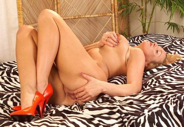 Старая блондинка с большой грудью на кровати ласкает пальчиками пизденку