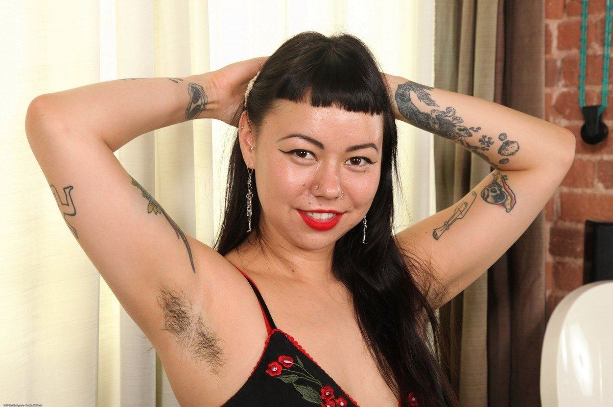Девушка с большим количеством татуировок на теле показывает себя с разных сторон и дает рассмотреть волосатую пизденку