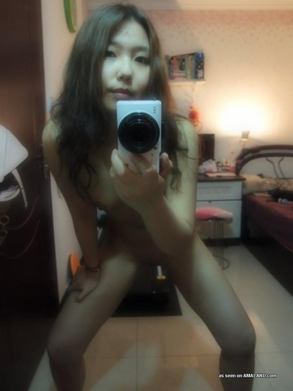 Миленькая азиатка с маленькими сиськами позирует голой перед зеркалом