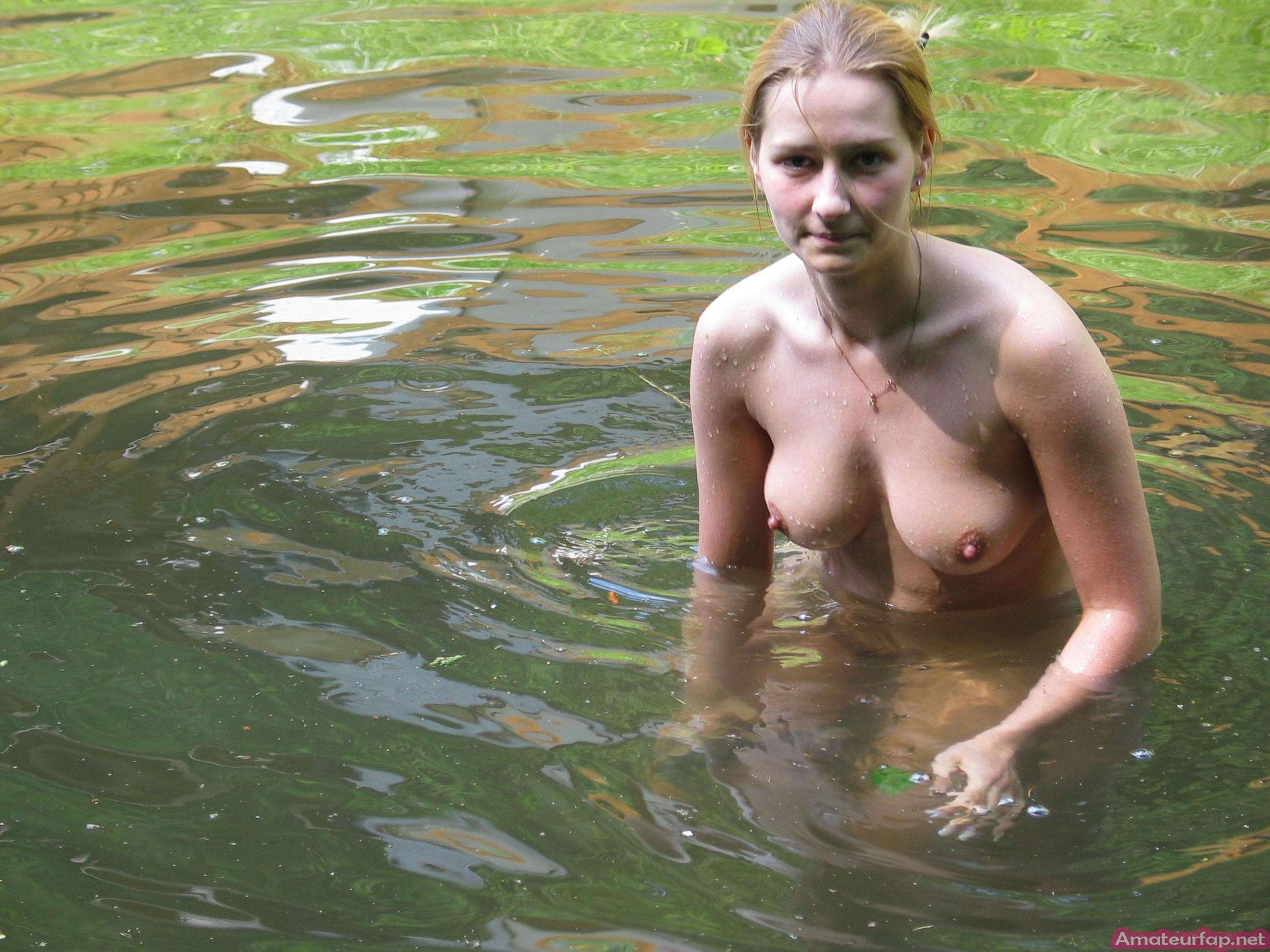 Блондинка плескается в озере голой