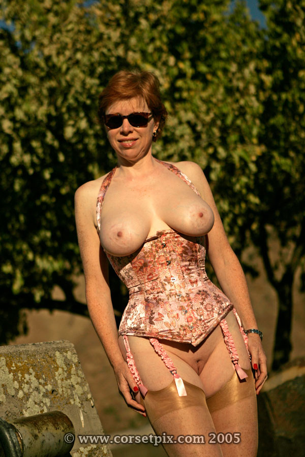 Женщина в корсете с голыми сиськами и пиздой